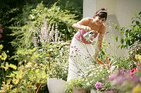 A woman standing in her garden watering plants