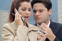 Young woman talking on the mobile phone holding a credit card with a young man
