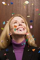 Businesswoman under falling confetti