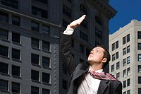 Businessman looking up at sunlight