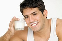 Smiling young man with milk mustache and holding glass of milk, close-up