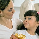 Woman and girl with gift, close-up, background people, selective focus