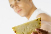 A Young man holding out a pineapple slice