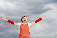 Senior adult woman with arms up in the air
