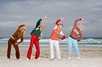 Four senior adults stretching on beach