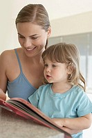 Mother helping her daughter to read