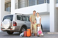 Family stood by car with suitcases
