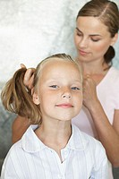 Mother styling her daughters hair