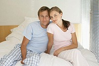 Portrait of mid adult couple sat on their bed