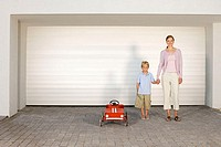 Mother and son stood by toy car