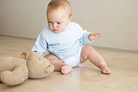 Baby reaching for a teddy bear