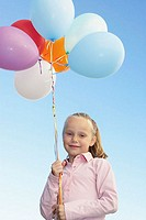 Young girl holding a bunch of balloons