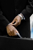 Businessman holding briefcase, close-up of hand and briefcase