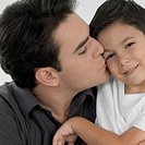 Close-up of a father kissing his son