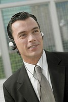 Close-up of a businessman listening to music on headphones