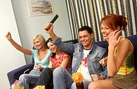 Mid adult man with two mid adult women watching television