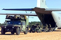 FORT POLK, La -- Airmen and Soldiers load cargo onto a C-130J Hercules during a Joint Readiness Training Center exercise. The center here focuses on i...