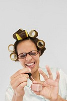 Smiling young woman in curlers polishing her fingernails