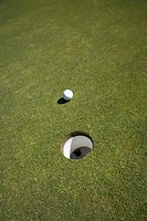 High angle view of a golf ball near a hole on a golf course