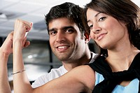 Close-up of a young man and young woman showing their biceps