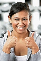 Portrait of a young woman giving thumbs up sign