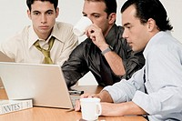Three businessmen sitting in front of a laptop