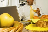 Businessman sitting at a dining table with a laptop