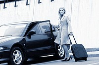 Businesswoman opening a car door, holding a bag