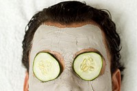 Man lying with face pack and cucumber slices on eyes, close-up