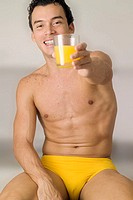 Man in yellow swimming trunks holding glass of orange juice, close-up