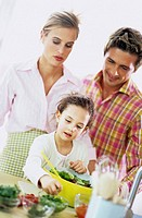 Parents watching daughter (6-7) prepare salad