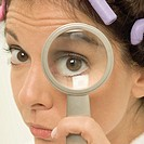 Woman in curlers looking through magnifying glass, extreme close-up