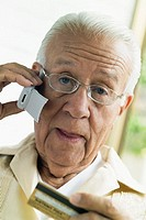 Senior man talking on cell phone and holding credit card, close-up, part of