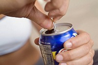 Extreme close-up of woman opening canned drink, focus on foreground
