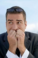 Worried looking businessman with hands in front of mouth, close-up
