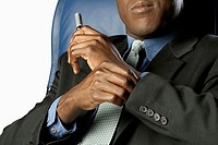 Mid section of Black businessman sitting in blue high back chair and holding a  pen, close-up, part of