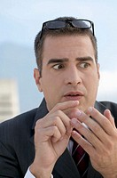 Businessman counting on fingers and looking stressed, close-up