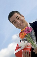 Smiling businessman holding bouquet of flowers and gift wrapped in red paper outdoors, extreme close-up