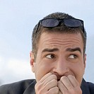 Worried businessman outdoors with hands covering mouth and eyeglasses on top of head, close-up