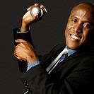 Smiling Black businessman holding stress ball against black background, close-up
