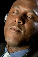 Black businessman sitting and listening to music through headphones, extreme close-up