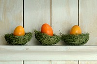 Orange Easter eggs lying on shelf on grass