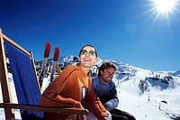 Couple relaxing on deckchair in alps ,smiling