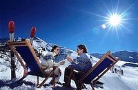 Man and woman clinking glasses, alps, winter