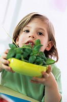 Boy (3-4) holding bowl of fresh basil, close-up, portrait