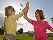 Women golfers doing a high five (thumbnail)