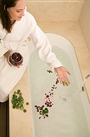 Woman dropping rose petals into bath