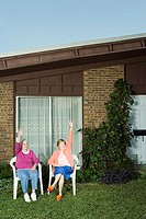 Two senior women sat in garden waving