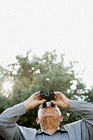 Senior man looking through binoculars (thumbnail)