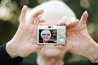 Senior woman taking a self portrait photograph (thumbnail)